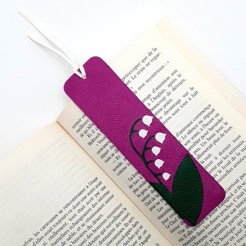 Marque-page en marqueterie cuir upcycling - Edition Spéciale Muguet de Mai - Fond Violet vert et pétales blancs sur livre